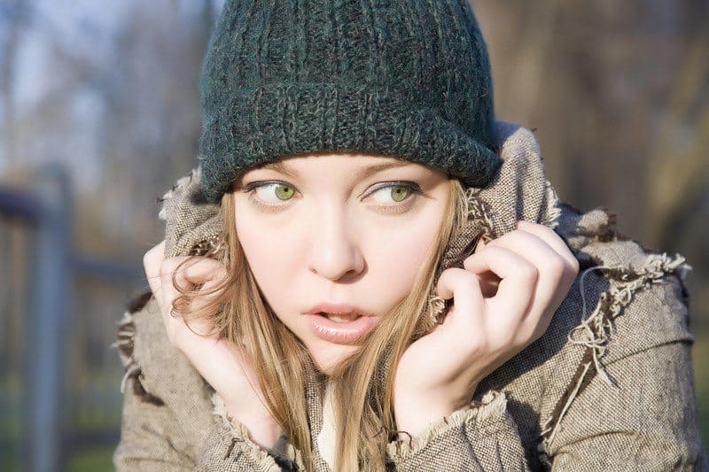 Woman in a beanie slouching with her hands around her face as if she is trying to shut out the world.