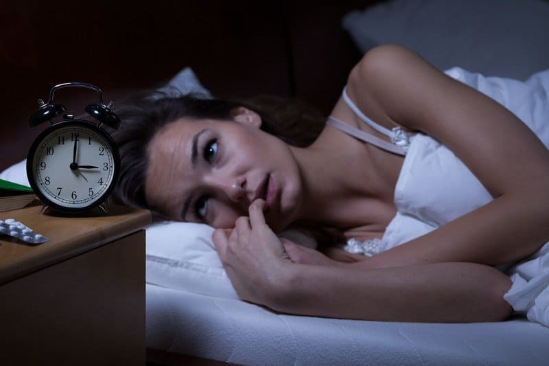 Woman lying in bed awake at night watching the clock.