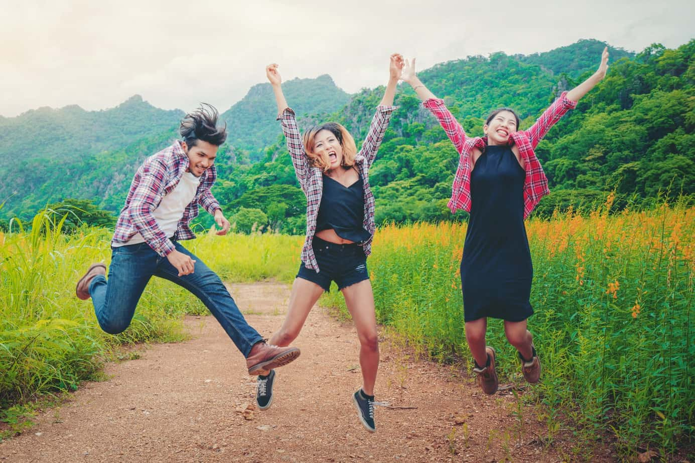 Group of happy young people jumping in the air while traveling in mountain and nature trail.