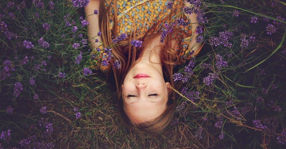 Girl lying on ground surrounded by lavender