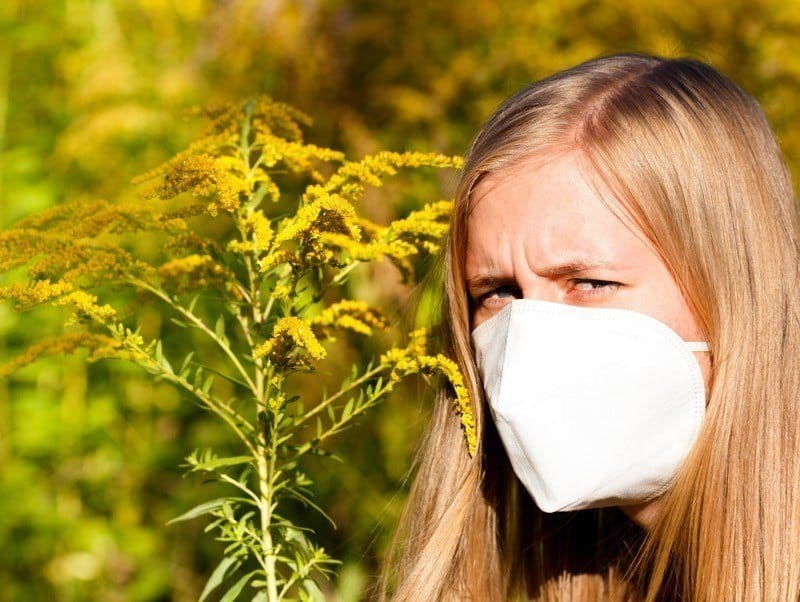 Girl with mask standing by goldenrod