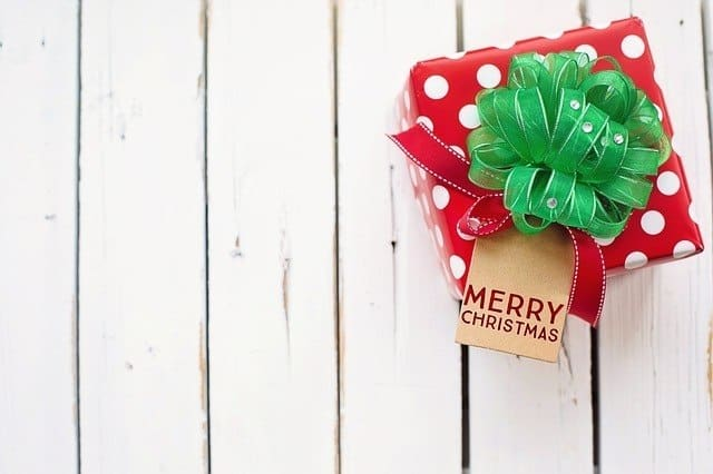 Red gift with green bow on a white wood background