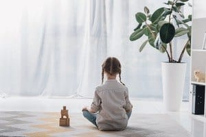 Little girl sitting alone on the floor with her back to the camera.