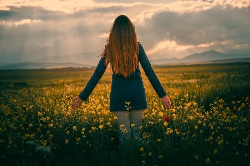 Woman in field of yellow flowers and sun rays streaming down from clouds in front of her