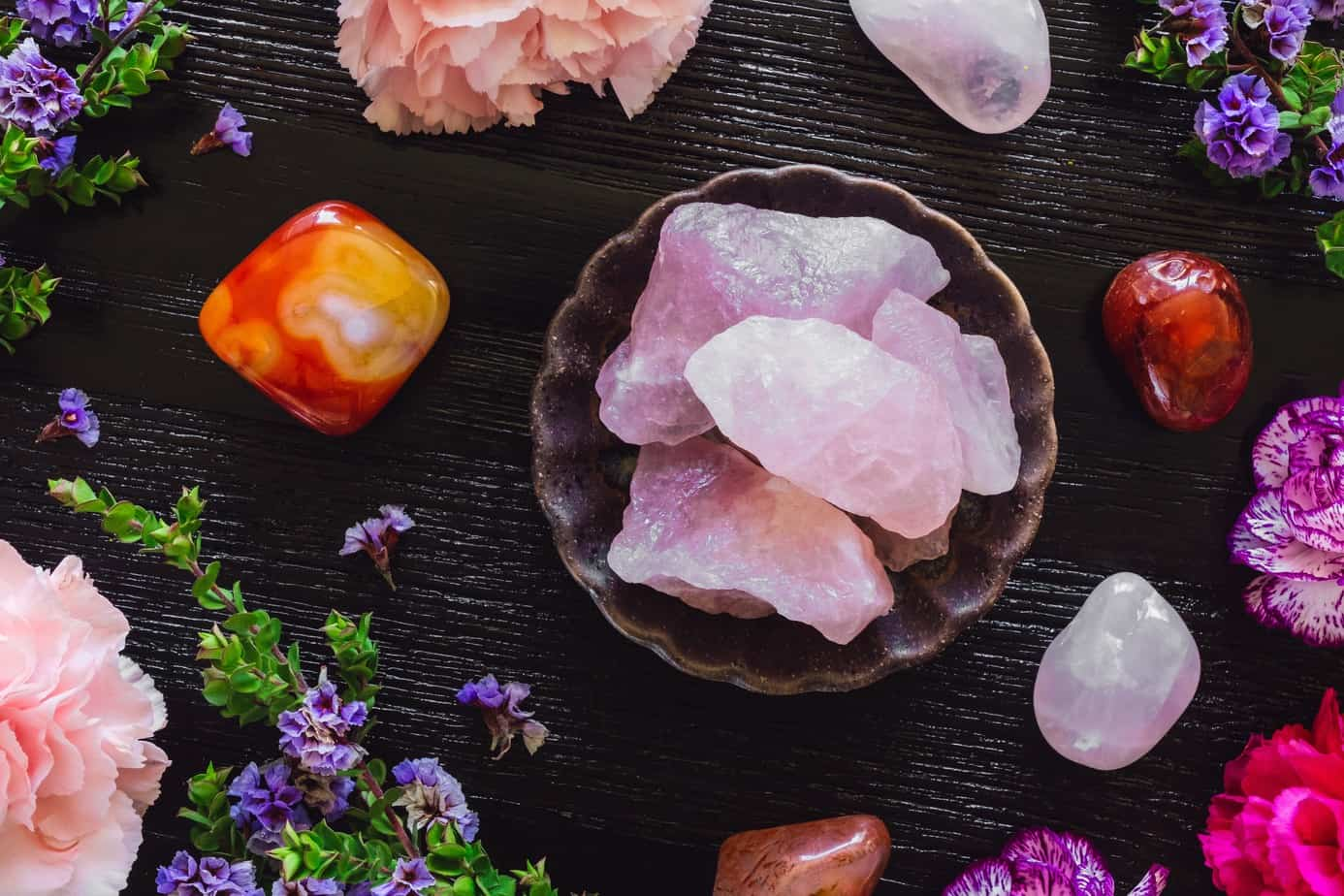 Rose Quartz and Carnelian on Dark Table with Carnations and Sea Lavender