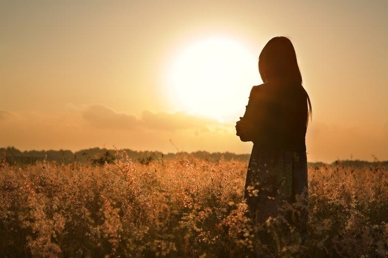 Woman standing in field of flowers, arms folded at sunset
